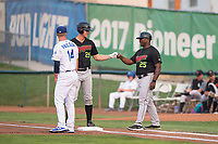 Great Falls Voyagers right fielder Logan Sowers (29) fist bumps with first base coach Eric Richardson (25) in front of first baseman Dillon Paulson (14) after getting a hit during a Pioneer League against the Ogden Raptors at Lindquist Field on August 23, 2018 in Ogden, Utah. The Ogden Raptors defeated the Great Falls Voyagers by a score of 8-7. (Zachary Lucy/Four Seam Images)