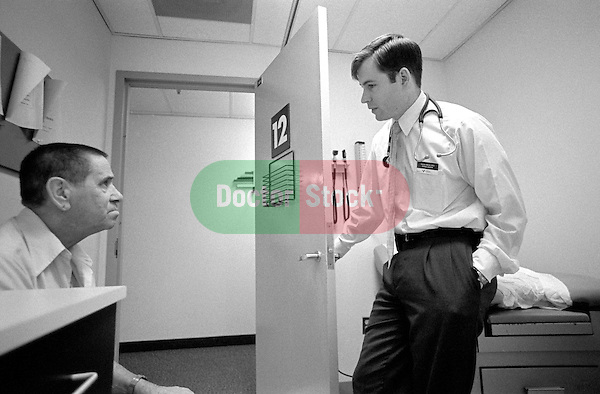 Elderly male patient and doctor conversing in examination room