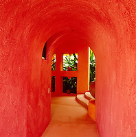 The curved hallway has a sculptural quality emphasised by the pink and orange walls