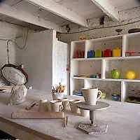 The interior of a craft studio with pottery peices and tools lying on a work bench. Colourful pieces of ceramics are displayed on shelving.