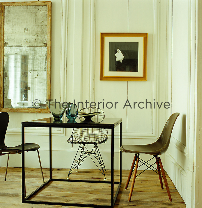 The dining room is furnished with four tables designed by Frederic Mechiche that come together as one dining piece and chairs by Eames, Bertoia and Jacobsen