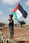 """Palestinian child waved the palestinian flag to celebrate the decision by the Israeli Supreme Court over the route of the controversial separation barrier being constructed by Israel in the occupied West Bank village of Bilin several kilometers from the city of Ramallah. Israel's Supreme Court ordered the state to re-route a section of its West Bank barrier at the village that has become a potent symbol of Palestinian opposition to the construction. The court ruled that the route of the separation barrier in the Bilin area was """"highly prejudicial"""" to the villagers and demanded that the government map out an alternative route """"within a reasonable period""""."""