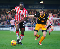 Lincoln City's John Akinde vies for possession with Newport County's Mark O'Brien<br /> <br /> Photographer Chris Vaughan/CameraSport<br /> <br /> The EFL Sky Bet League Two - Lincoln City v Newport County - Saturday 22nd December 201 - Sincil Bank - Lincoln<br /> <br /> World Copyright © 2018 CameraSport. All rights reserved. 43 Linden Ave. Countesthorpe. Leicester. England. LE8 5PG - Tel: +44 (0) 116 277 4147 - admin@camerasport.com - www.camerasport.com