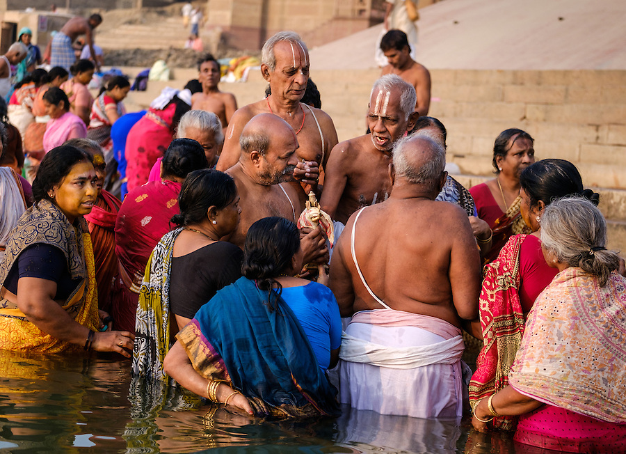 VARANASI, INDIA - CIRCA NOVEMBER 2016: Family worshiping and bathing in the Ganges river. Varanasi is the spiritual capital of India, the holiest of the seven sacred cities and with that many rituals and offerings are performed daily by priests and hindus.