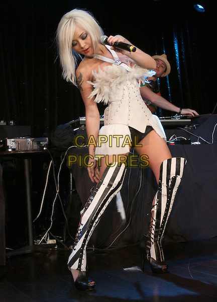 TILA TEQUILA .Tila Tequila Album Release party Performance held At The Conga Room, Los Angeles, California, USA, .12th May 2010..music performing performance on stage concert gig full length white strapless corset top ruffle skirt dress black striped otk knee thigh high boots lace-up heels  hand knickers hotpants tattoo microphone  feathers feather .CAP/ADM/KB.©Kevan Brooks/AdMedia/Capital Pictures.