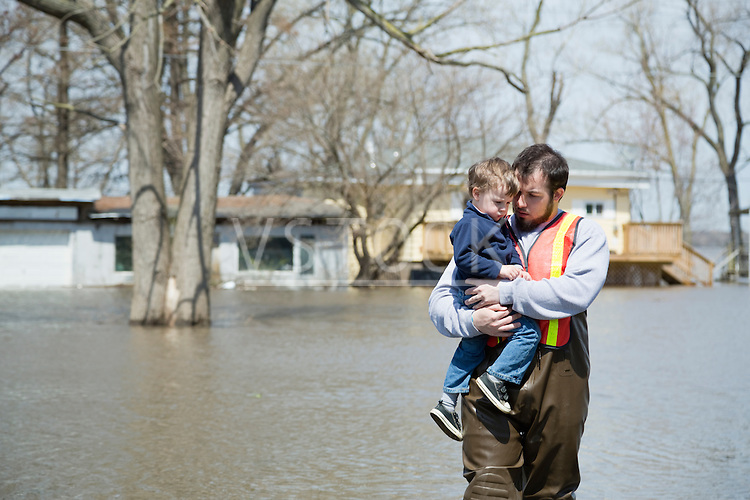 Man with son wading in floodwaters