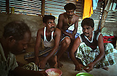 Four fishermen who lost their wives and children to the tsunami cook together in Mullaittivu, on the northeastern coast of Sri Lanka, an area ravaged also by civil war. .The December 26, 2004 tsunami killed around 40,000 people along Sri Lanka's southern, eastern and northern shores, tearing thousands of families apart. .The bulk of the dead were women and children - husbands lost young brides and around 4,000 children lost one or both parents. .Even before the tsunami struck, people here in the northeast had already been displaced four times by the Tigers' two-decade war for autonomy. .In some places, the scars of war and the tsunami have become one. Remnants of walls torn down by waves are pockmarked with bullet holes and shrapnel from shells fired before a 2002 ceasefire plunged a civil war that killed over 64,000 people into limbo. ..Picture taken March 2005 by Justin Jin