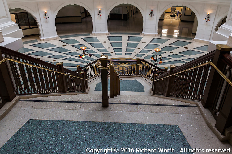 The grand staircase leads down to the equally grand ground floor level with geometric flooring and arches at the perimeter.