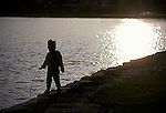 Child playing at water's edge
