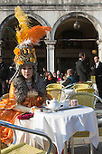 Venice, Italy, 8 February 2015. The mature women in costume. A woman in costume sits in one of the outdoor restaurants in St Mark's Square. People wear traditional masks and costumes to celebrate the 2015 Carnival in Venice. carnivalpix/Alamy Live News