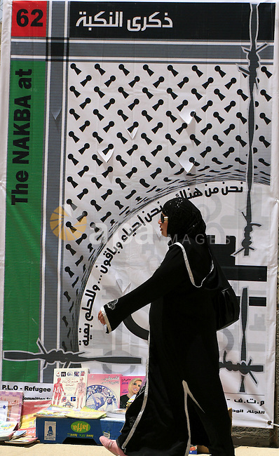 "A Palestinian woman walks past a poster made for the 62nd anniversary of the ""Nakba"" (catastrophe) in the West Bank city of Ramallah on May 8, 2010. Nakba is what the Palestinians call the creation of the state of Israel in May 1948, which led to 750,000 Palestinians being driven out or fleeing their homes. photo by Issam Rimawi"