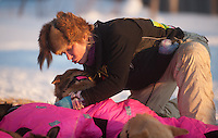 DeeDee Jonrowe cares for her team after arriving in the Kaltag checkpoint during the 2011 Iditarod.