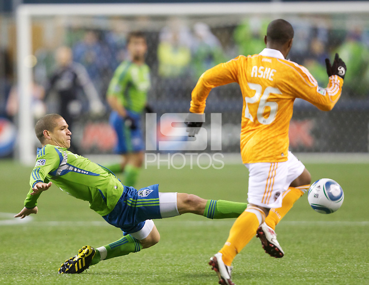 Seattle Sounders FC midfielder Osvaldo Alonso  kicks the ball away from Houston Dynamo forward Corey Ashe during play at Qwest Field in Seattle Friday March 25, 2011. The match ended in a 1-1 draw.