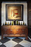 The entrance hall is furnished with an early 18th century Dutch oakwood chest on which is displayed a row of antique glass bottles.  The painting is by the Belgian realist Van Cotthem and dated 1986