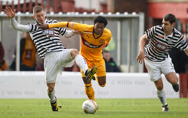 Omar Daley uses his strength to force his way past Queens defenders Darryl Meggatt and James Brough to score for Motherwell