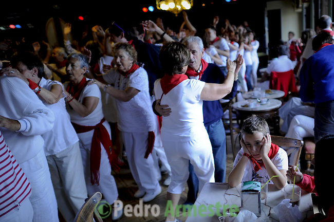 A bored child sits at a table while people dance in the casino of Pamplona after the fifth San Fermin Festival bull run, on July 11, 2012, in Pamplona, northern Spain. The festival is a symbol of Spanish culture that attracts thousands of tourists to watch the bull runs despite heavy condemnation from animal rights groups(c) Pedro ARMESTRE