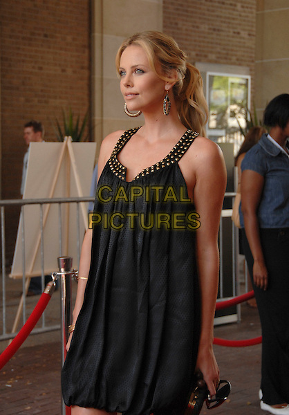 "CHARLIZE THERON.Arrives at The 32nd Annual Toronto International Film Festival for the ""Battle in Seattle"" Premiere in Ryerson.Toronto, Ontario Canada, September 8, 2007..half length black dress gold studded collar ponytail earrings hoops.CAP/TL.©Tony Lee/Capital Pictures."