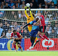 Lincoln City's Josh Vickers saves under pressure from  Wycombe Wanderers' Adebayo Akinfenwa, with support from Jason Shackell, right<br /> <br /> Photographer Andrew Vaughan/CameraSport<br /> <br /> The EFL Sky Bet League One - Wycombe Wanderers v Lincoln City - Saturday 7th September 2019 - Adams Park - Wycombe<br /> <br /> World Copyright © 2019 CameraSport. All rights reserved. 43 Linden Ave. Countesthorpe. Leicester. England. LE8 5PG - Tel: +44 (0) 116 277 4147 - admin@camerasport.com - www.camerasport.com