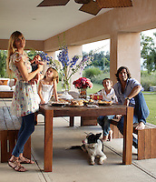 Nacho Figueras with his wife Delfina, their children and dog relax on the covered terrace of their stud farm near Buenos Aires