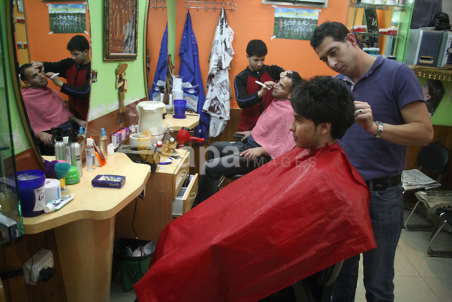 Palestinian barbers cut hair for youths at a shop in the West Bank city of Hebron on 14 November 2010, in preparation for the Muslim holiday of Eid al-Adha or the Feast of Sacrifice, which marks the end of the annual pilgrimage. Photo by Najeh Hashlamoun