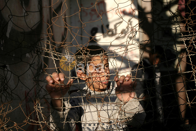 A Palestinian boy looks on as he plays at the street in Rafah refugee camp in the southern Gaza Strip, February 08, 2014. Photo by Eyad Al Baba