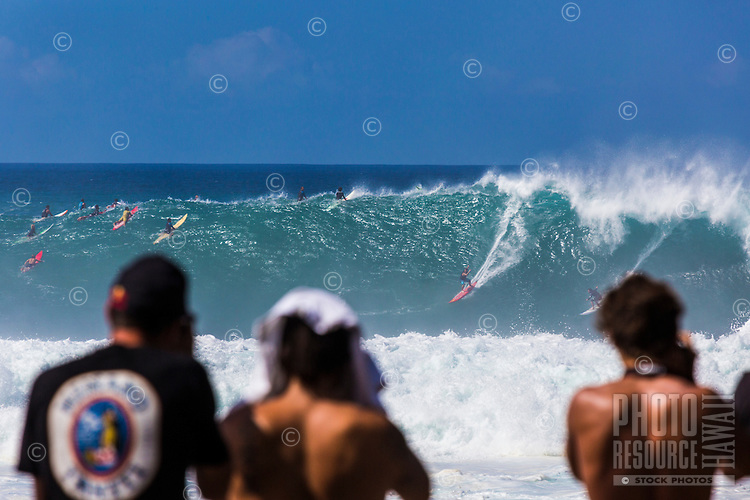 Tourists and photographers watch the big wave surfing scene at Waimea Bay, North Shore, O'ahu.
