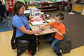 MR / Schenectady, NY. Zoller Elementary School (urban public school). Kindergarten inclusion classroom. Paraprofessional does assessment of kindergarten math skills for student (boy, 5, with hearing aid). MR: You6, Sch20. ID: AM-gKw. © Ellen B. Senisi.