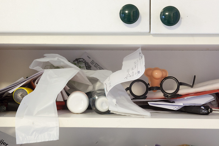 The shelf in our kitchen accumulates many household items, including birthday party souvenirs.