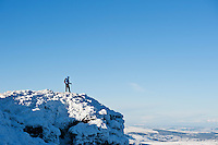 Female hiker stands on summit of Corn Du in winter, Brecon Beacons nationl park, Wales