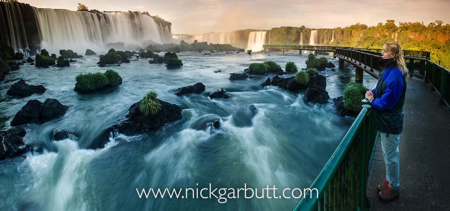 Tourist (Barbara Heathcote) looking at upper Iguazu Falls (also Iguazú Falls, Iguassu Falls or Iguaçu Falls) at sunrise. Argentina / Brazil border. Photographed from the Brazilian side.