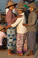 Three young women from the fishing village of Jade Taw on the Bay of Bengal in Myanmar who are waiting on the beach for the morning's catch to be brought ashore, their faces daubed in the thanaka bark paste that the Burmese use to protect their skin from the fierce sun, turn to face the camera.