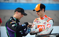 Nov. 13, 2009; Avondale, AZ, USA; NASCAR Sprint Cup Series driver Denny Hamlin (left) talks with teammate Joey Logano during qualifying for the Checker O'Reilly Auto Parts 500 at Phoenix International Raceway. Mandatory Credit: Mark J. Rebilas-