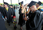 Tammy Kinsley helps Dustin Cheney adjust his cap before the Western Nevada College commencement at the Pony Express Pavilion, in Carson City, Nev., on Monday, May 19, 2014. Cheney's son Levy, 2, is at center.<br /> Photo by Cathleen Allison/Nevada Photo Source