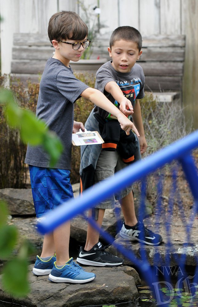 NWA Democrat-Gazette/DAVID GOTTSCHALK McCoy Box (left) and Elijah Lopez, both third grade students from Bernice Young Elementary School, participate in a scavenger hunt Thursday, October 4, 2018, during Butterfly Days 2018 at the Botanical Garden of the Ozarks in Fayetteville. First through third grade students participated in the four day event that corresponded with science and biology curriculum at the school and featured  seven education stations about butterflies.