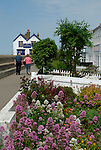 Seafront cottages and Old Neptune pub with passing middle aged couple, Whitstable, Kent, England