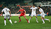 SWANSEA, WALES - MARCH 16: Joe Allen of Liverpool (2nd L) attempts to get past Jack Cork (3rd L) and Jordi Amat (R) of Swansea during the Premier League match between Swansea City and Liverpool at the Liberty Stadium on March 16, 2015 in Swansea, Wales