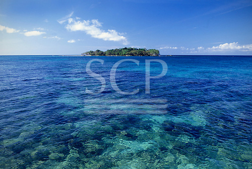 Negril, Jamaica. The island of Booby Cay at the end of Long Bay Beach. Tropical island with clear green water, rocks visible.