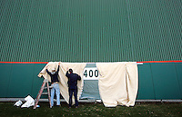 Brad Justice, left, and Sid Blackwell hang a drop cloth over the outfield wall of Doug Kingsmore Stadium as they prepare to paint the distance marker on it Thursday. The Clemson University baseball team begins its season with three games over the weekend starting today against Miami (Oh) at 4 p.m. Baseball fans will be able to enjoy warmer weather as they watch the Tigers as forecasters are calling for temperatures to reach into the 60s on Saturday and Sunday.