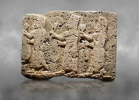 Hittite monumental relief sculpted orthostat stone panel of a Procession Limestone, Karkamıs, (Kargamıs), Carchemish (Karkemish), 900-700 B.C. Anatolian Civilisations Museum, Ankara, Turkey.<br /> <br /> It is a depiction of three marching female figures in long dress with a high headdress at their head. These women are considered to be the nuns of the Goddess Kubaba. The figures in the front and behind have a round mirror in their right hand while the figure in the middle has a bunch of spica in her right hand. Figures carry objects similar to a sceptre in their left hand.  <br /> <br /> Against a grey art background.