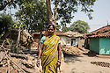 """Gurubari Mahato, 35 years old, from  Dhatkidih, photographed between her house and the house of the accusers. In 2009, she was accused of witchcraft by a bride living in the same village, who fell sick just hours before her marriage. After being attacked and threatened with rape by the bride's brother, she finally had her case dismissed during a village meeting. """"I just saved myself because I had enough money to keep on fighting against my accusers. Otherwise, I would have faced so many problems""""."""