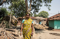 "Gurubari Mahato, 35 years old, from  Dhatkidih, photographed between her house and the house of the accusers. In 2009, she was accused of witchcraft by a bride living in the same village, who fell sick just hours before her marriage. After being attacked and threatened with rape by the bride's brother, she finally had her case dismissed during a village meeting. ""I just saved myself because I had enough money to keep on fighting against my accusers. Otherwise, I would have faced so many problems""."