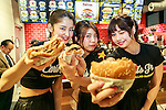 Members of staff pose for a photograph during the pre-opening event for the Japan's first Carl's Jr. burger restaurant located in Tokyo's Akihabara district, on March 2, 2016, Japan. The Californian fast food restaurant follows on the heels of Shake Shack in entering the Japanese market. Mitsuuroko Group Holdings Co., Ltd. has signed a franchise agreement to operate Carl's Jr. branches in Japan with the first to open to the public on March 4th. (Photo by Rodrigo Reyes Marin/AFLO)