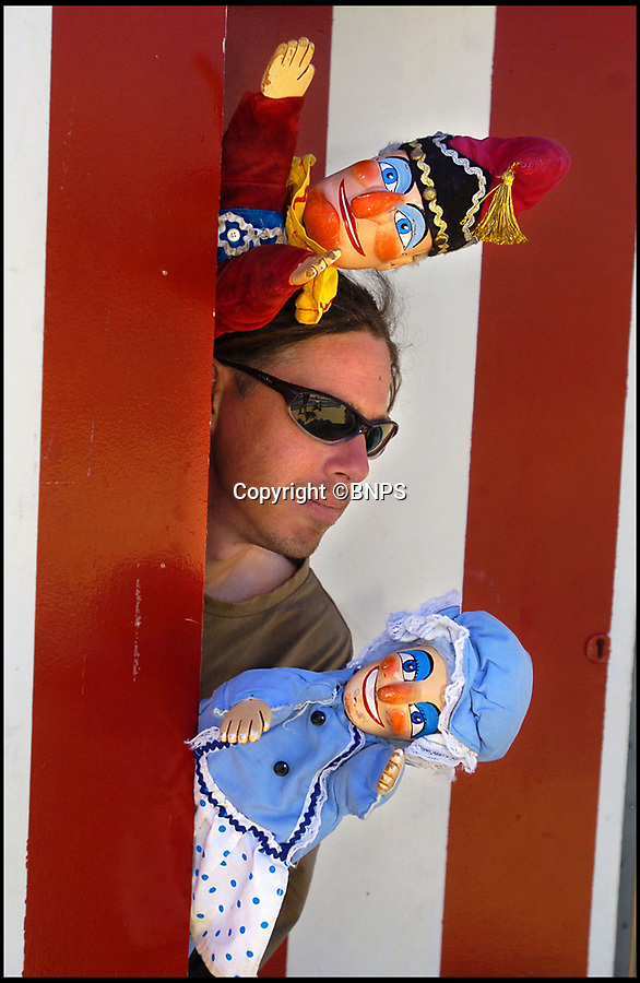 BNPS.co.uk (01202 558833)Pic: PhilYeomans/BNPS<br /> <br /> Mark Poulton with his puppets Punch and Judy on Weymouth beach.<br /> <br /> One of Britain's longest-running Punch and Judy shows is in jeopardy because the man behind it says he cannot afford to keep it going.<br /> <br /> Mark Poulton, who runs the show in Weymouth, Dorset, said a shorter holiday season has hit his takings but his expenses and overheads remain the same.<br /> <br /> He blamed strict rules preventing parents from taking their children out of school during term-time, reducing his usual 17-week season to just seven weeks, and said school groups have also stopped coming in July due to budget cuts.<br /> <br /> The seaside town has had a Punch and Judy show since 1880, but Mr Poulton says he relies on donations and with audiences dwindling he will not be able to continue the seaside tradition past this summer season without outside support.