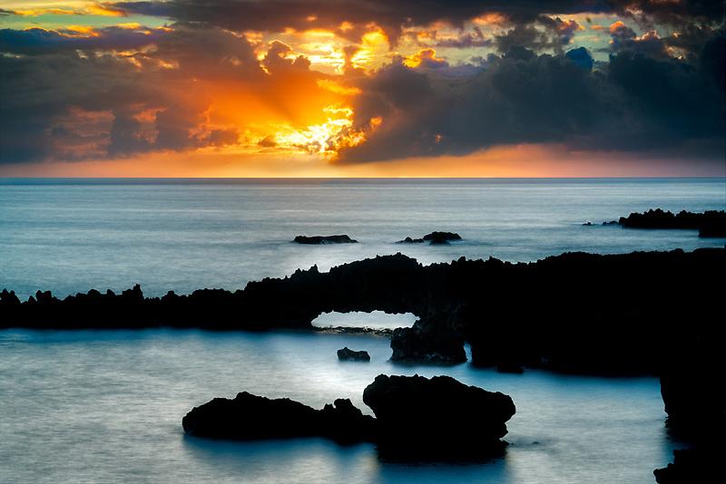 Arch and sunrise at Black Sand Beach overlook. Waianapanapa State Park, Maui, Hawaii.