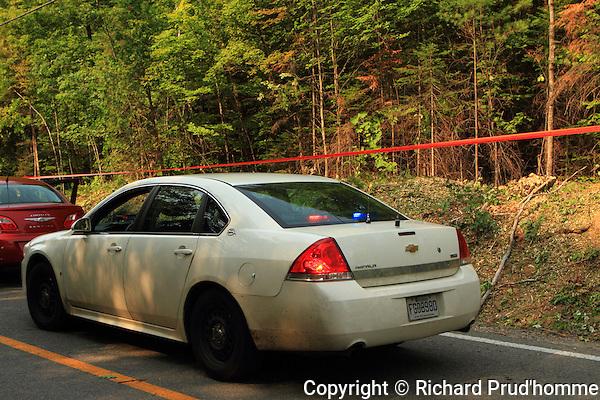 A white unmark police car at a crime scene