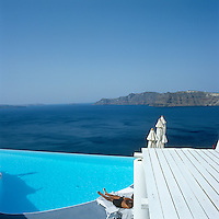 A man lies on a sun lounger beside an infinity pool with a view of the Mediterranean beyond