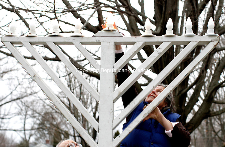 Middlebury, CT- 16 December 2014-121614CM06-   Elaine Strobel of Middlebury, lights the Menorah during the annual Menorah Lighting on the Middlebury Green on Tuesday. The ceremony was arranged by the Middlebury Congregational Church, which owns the Green, and Westover School, whose maintenance staff sets up the menorah, as a gift to their Jewish neighbors.   Christopher Massa Republican-American