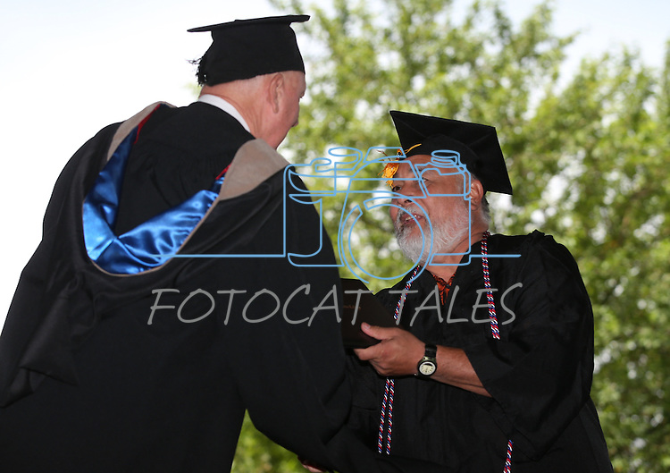 Interim President Chester Burton congratulates James Rocha during the Western Nevada College commencement at the Pony Express Pavilion, in Carson City, Nev., on Monday, May 19, 2014. <br /> Photo by Cathleen Allison/Nevada Photo Source