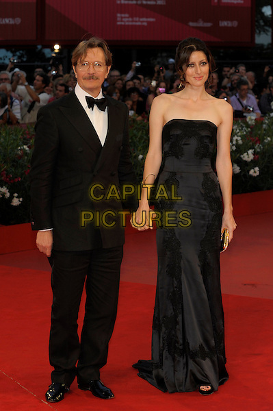 Gary Oldman & Donya Fiorentino.The 'Tinker, Tailor, Soldier, Spy' premiere at the Palazzo del Cinema during the 68th Venice Film Festival, Venice, Italy..September 5th, 2011.full length black tuxedo dress married husband wife strapless holding hands.CAP/PL.©Phil Loftus/Capital Pictures.