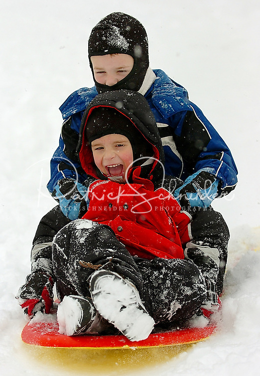 Kids make the most of a snowstorm by sledding. Photo taken in Avery County in the North Carolina Blue Ridge Mountains.